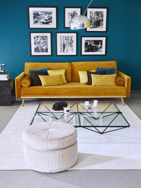 Petrolfarbene Wand im Wohnzimmer mit gelbem Sofa, weißem Teppich und Pouf