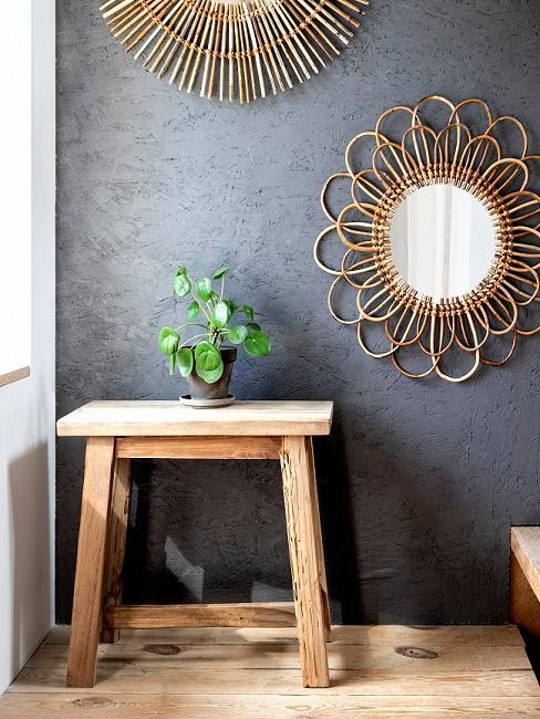 Schwarze Wand im Flur mit goldenem Spiegel und Hocker aus Holz