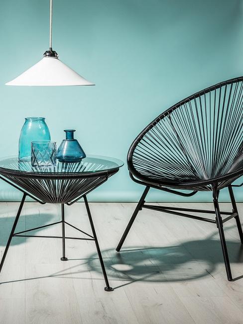 Wandfarbe Türkis mit schwarzem Beistelltisch und Acapulco Chair aus Rattan