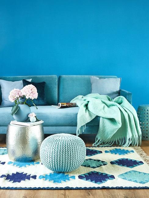 Dunkles Türkis im Wohnzimmer mit türkisblauer Couch und Kissen, Decke und Teppich