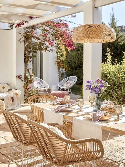 Terrasse mit Esstisch aus Holz und Stühlen und Beleuchtung aus Rattan