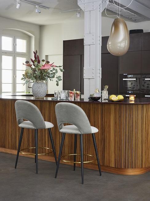 Schwarze Küche mit Kücheninsel aus dunklem Holz und zwei grauen Samtstühlen