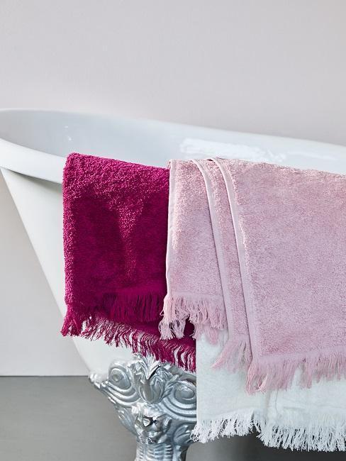 bañera blanca con toallas violetas