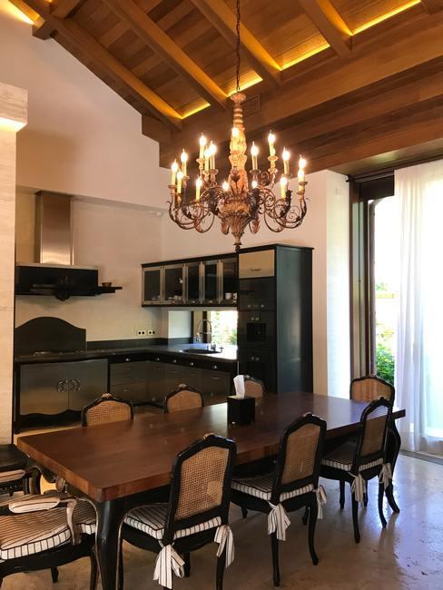 Cocina grande en una casa de aspecto campestre con una lámpara de araña encima de una mesa de madera
