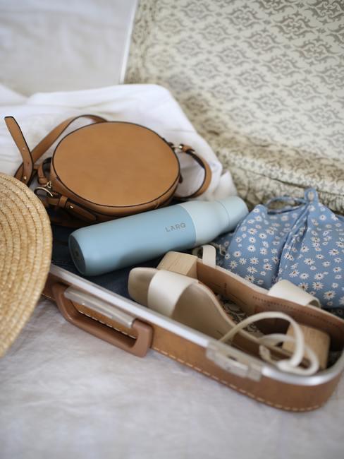 Maleta pequeña en cuero marrón con sandalias, botella y algo de ropa