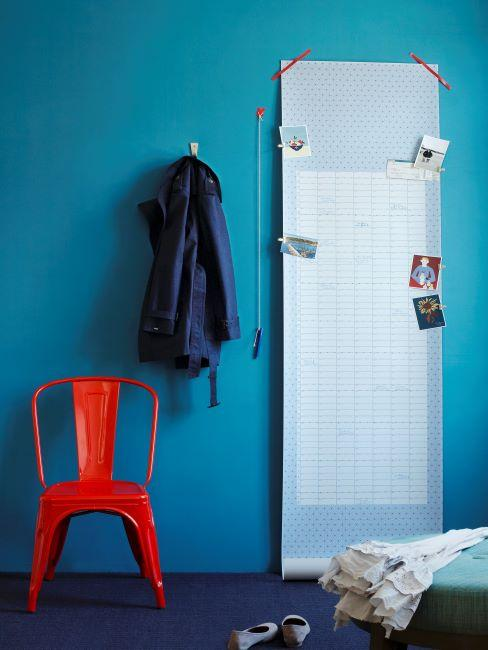 Chaise à accoudoirs en métal rouge et miroir contre mur bleu