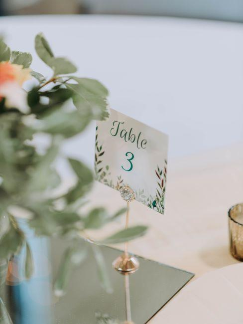 Carton marqueur de table sur support et bouquet de fleurs