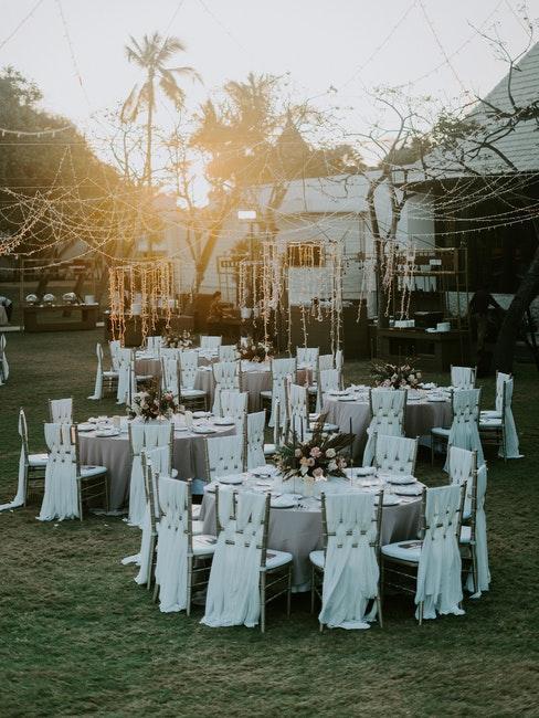 Tables mariage rondes decorees de blanc et guirlandes lumineuses