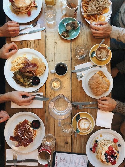 Table en bois avec vaisselle blanche et de nombreux plats a deguster