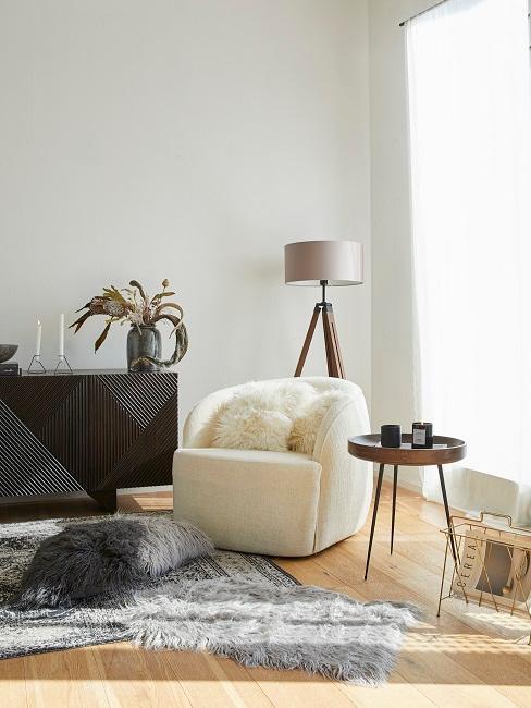 Soggiorno di design in Natural Living Style con poltrona beige e cuscini e coperte in pelliccia artificiale.