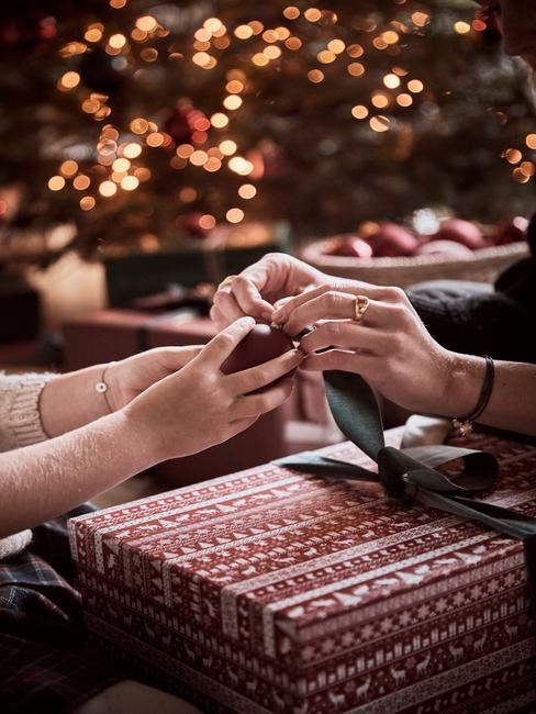 rood cadeau met handen en groen lint