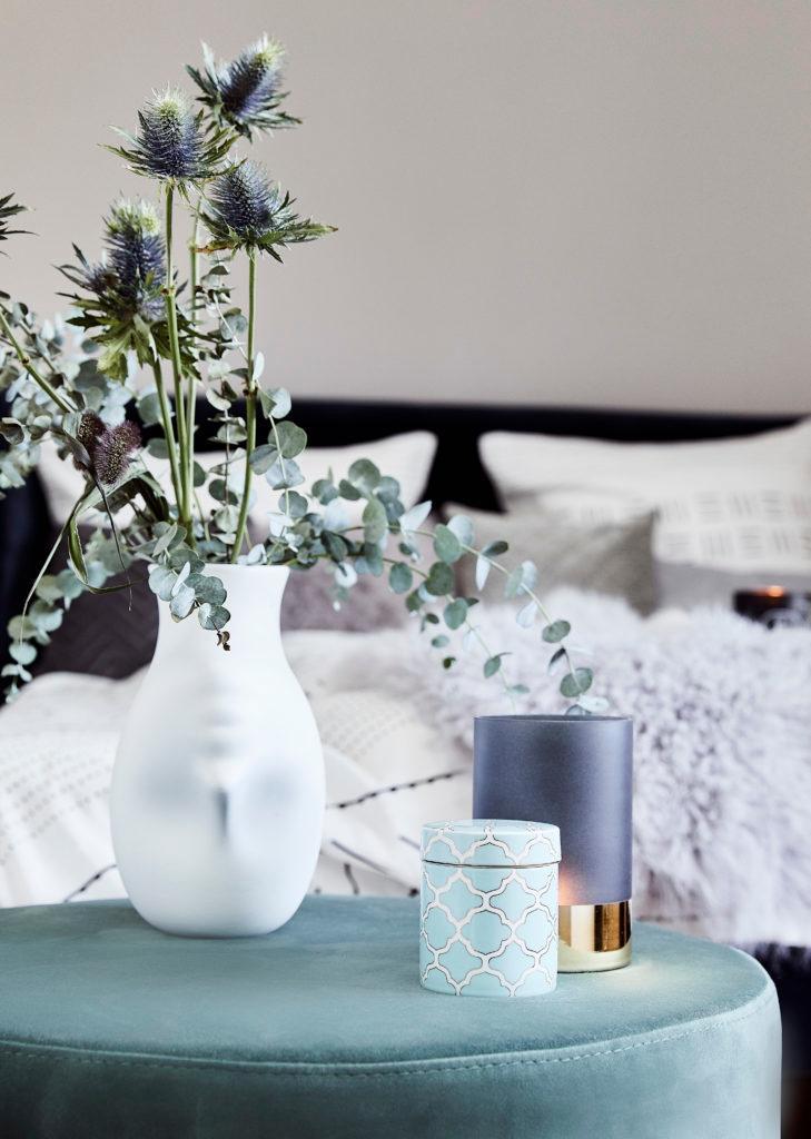 Eukaliptus w białym wazonie, obok świece zapachowe