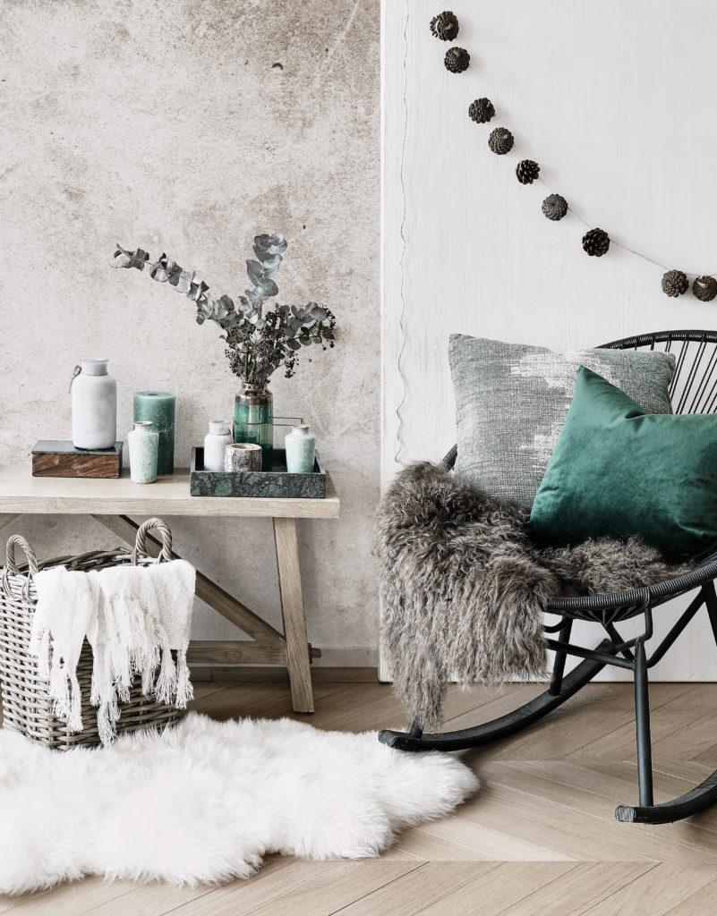 Kącik zdrewnianą ławą i fotelem na biegunach urządzony w odcieniach szarości i szałwiowej zieleni