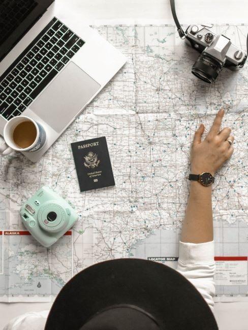 Osoba siedząca przy stole na którym leży rozłożona mapa, komputer, paszport oraz aparat