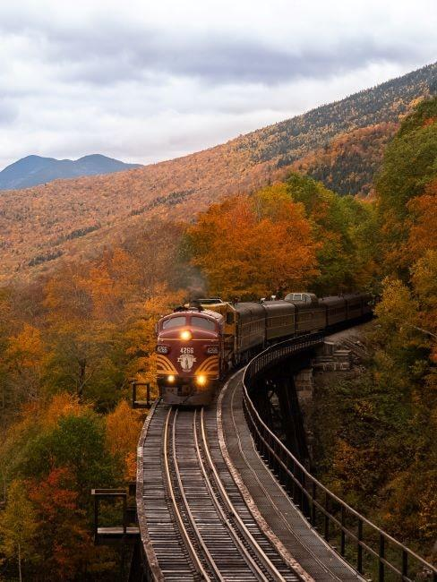 Pociąg jadący pomiędzy wzgórzami w trakcie jesieni