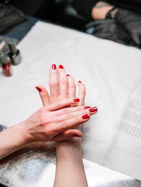 Jak dbać o paznokcie- kobiece dłonie z czerwonymi paznokciami