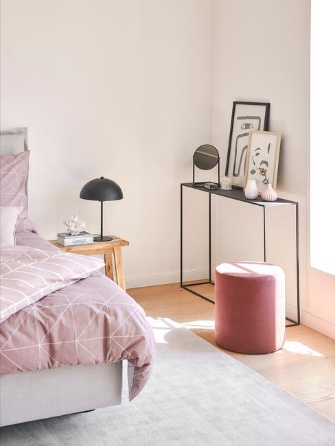 Fragment sypialnia z łożkiem, metalową otwartą półką z dekoracjami i różowym pufem