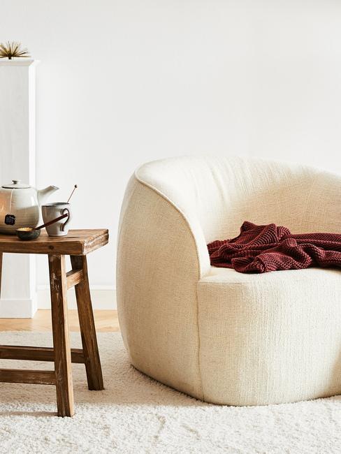 Zbliżenie na kremowy fotel, drewniany stolik z filiżankami i imbrykiem
