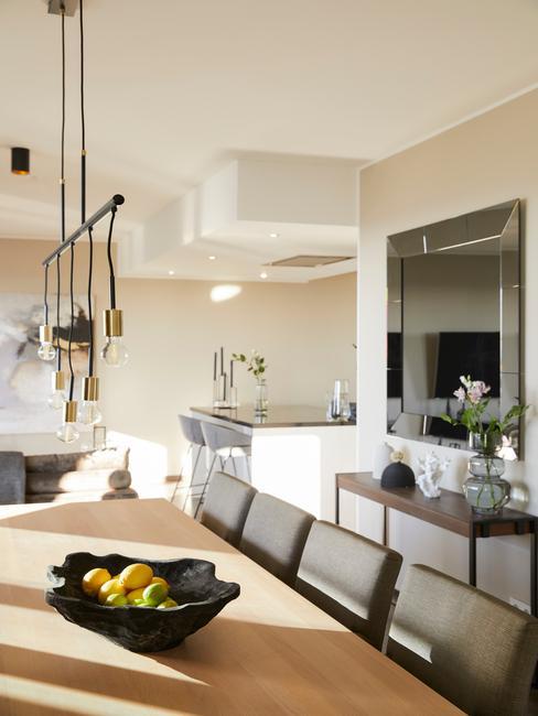 wnętrze jasnej jadalni z dużym, drewnianym stołęm, szarmi krzesłami, lustrem oraz wisząca lampą