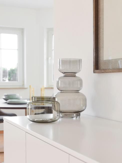 Dwa wazony postawioane na białej komodzie w minimalistycznym wnętrzu