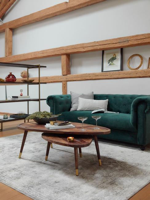Salon w stylu rustykalnym z drewnianymi belkami, szmagardową sofą, drewnianym stolikiem oraz metalową półką