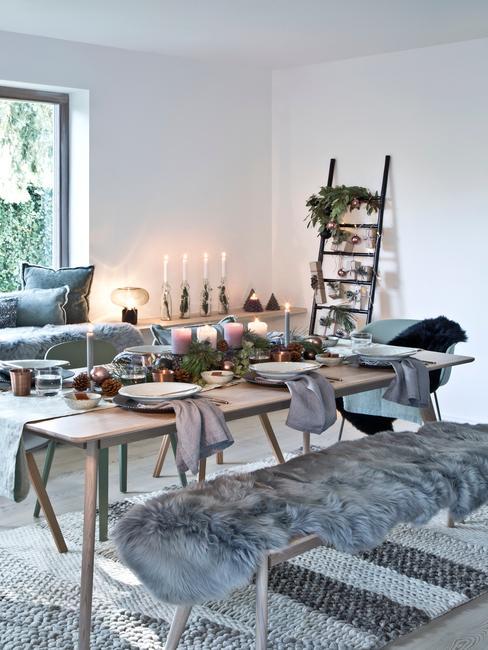 Jadalnia z drewnianym stołem, szarymi tekstyliami oraz udekorowaną drabiną