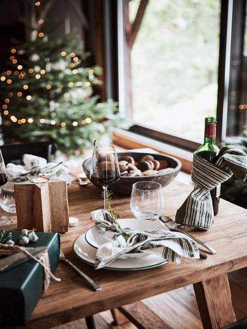 Fragment jadalni z drewnianym stołem i ubraną choinką oraz białą zastawą na stole