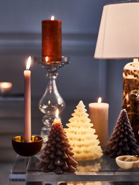 Stolik kawowy udekorowany świeczkami w kształcie choinki, świecznikiem, długą świecą oraz lampą