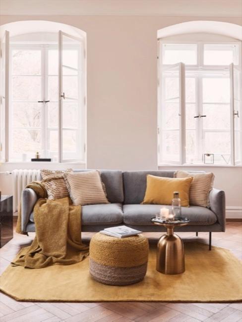 Szara sofa w salonie z musztardowymi akcentami dekoracyjnymi, takimi jak poduszki, koc, dywan i puf