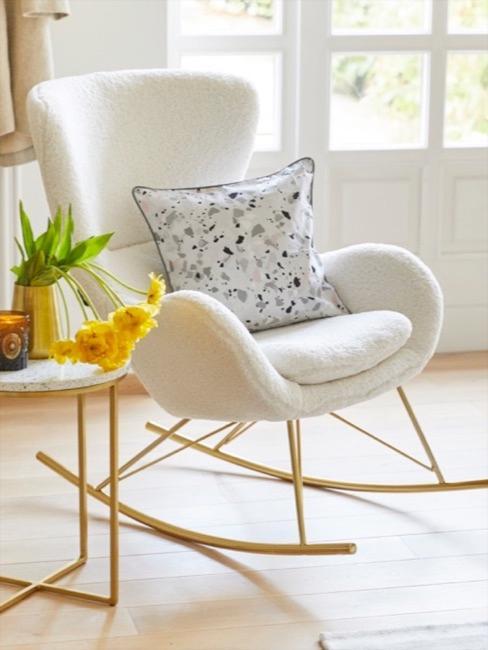 Jasny fotel bujany z poduszką z motywem lastriko, obok wazon z tulipanami