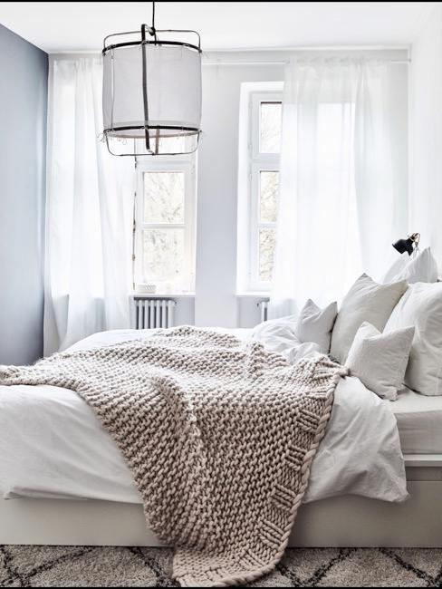 Cama deshecha en tonos crema y blanco, con dos grandes ventanales al findo y una gran lámpara colgando encima de la cama
