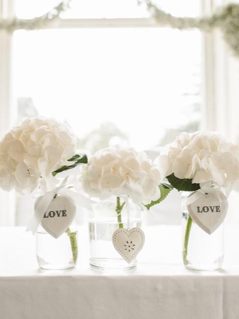Déco mariage mariage : Hortensias blancs décorés de cœurs dans des vases en verre