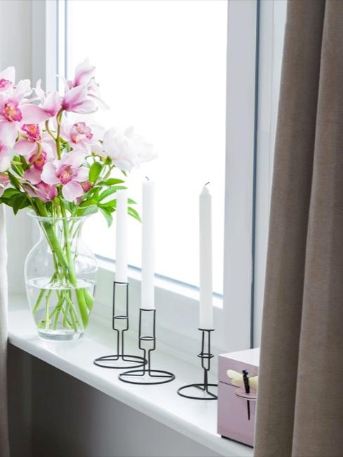 Różowa dekoracja okienna z wazonem na kwiaty, świecami i biżuterią.