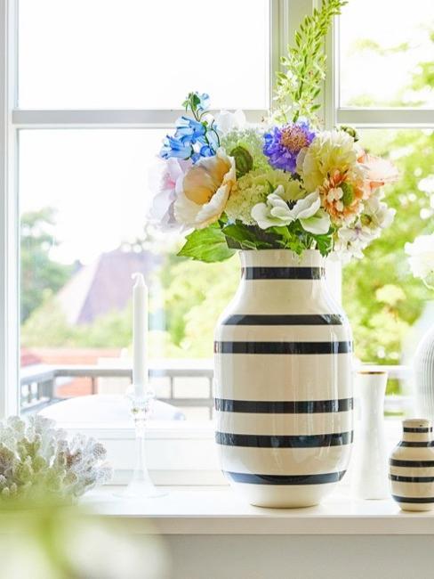 Dekoracje okienne na wiosnę z wazonami, świecami i kolorowymi kwiatami.