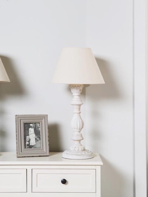 Commode à tiroirs avec lampes à poser claires et cadres dans le style shabby chic