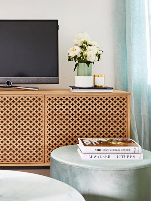 Drewniana komoda z telewizorem i miętowe pufy z albumami.