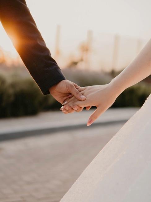 Close-up bruiloftspaar die handen vasthoudt