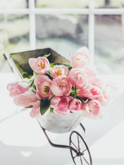 Bloemendecoratie van tulpen en klein kruiwagentje
