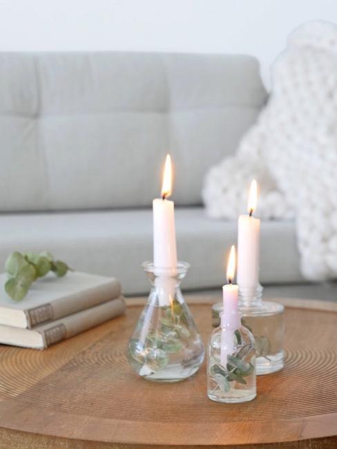 Salón con sofá gris y mesa de madera con portavelas de cristal