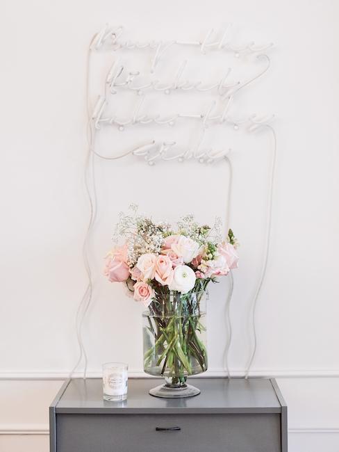 Beistelltisch mit Blumen in Vase und Leuchtschrift darüber