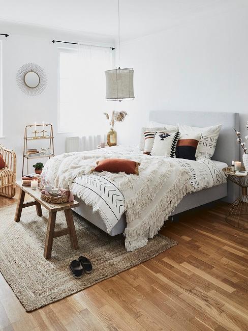 Schlafzimmer im Ethno Style mit Kissen und Decke