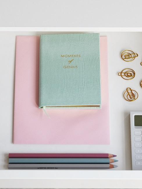 Bullet Journal couleur menthe, rangé dans le tiroir du bureau, accompagné de 3 crayons