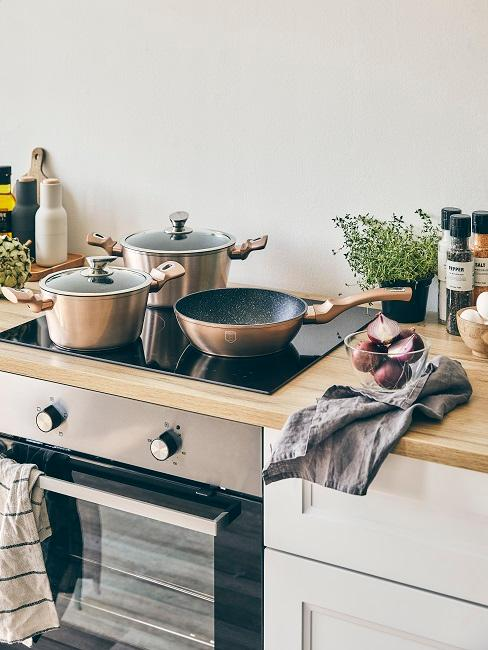 Piekarnik, garnki i patelnia na blacie kuchennym oraz ścierki i inne przybory kuchenne.