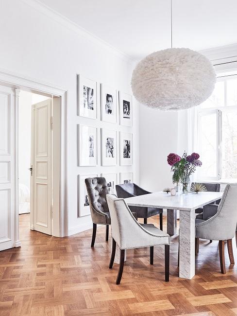 Witte hanglamp boven de eettafel met boeket bloemen in glazen vaas