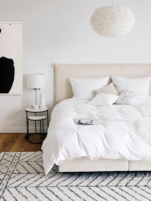 Dormitorio con una lámpara de plumas XXL, en blanco