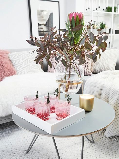 Verres à whisky roses sur table d'appoint grise avec bouquet de fleurs