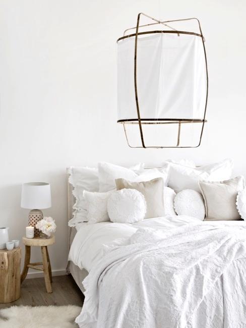 Helles Schlafzimmer mit Holzhocker als Nachttisch