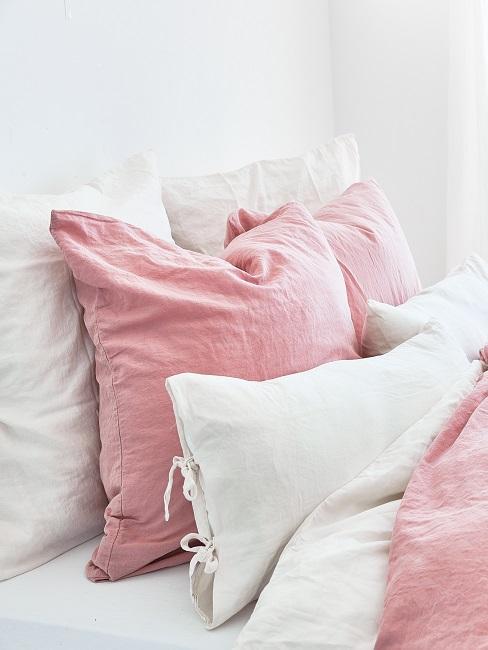 Lit avec linge de lit blanc et rose dans la chambre à coucher