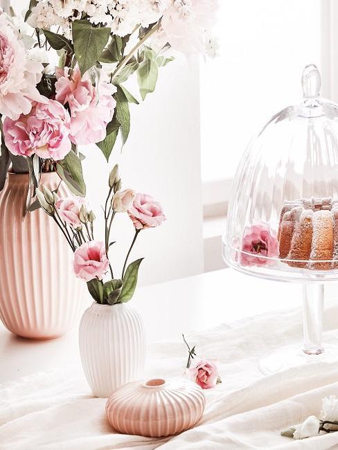 Stół zastawiony kwiatami w wazonach oraz patera z ciastem.