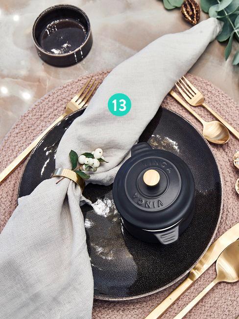 Zastawa stołowa z talerzami, sztućcami i serwetką lnianą ze złotym pierścieniem do serwetek.